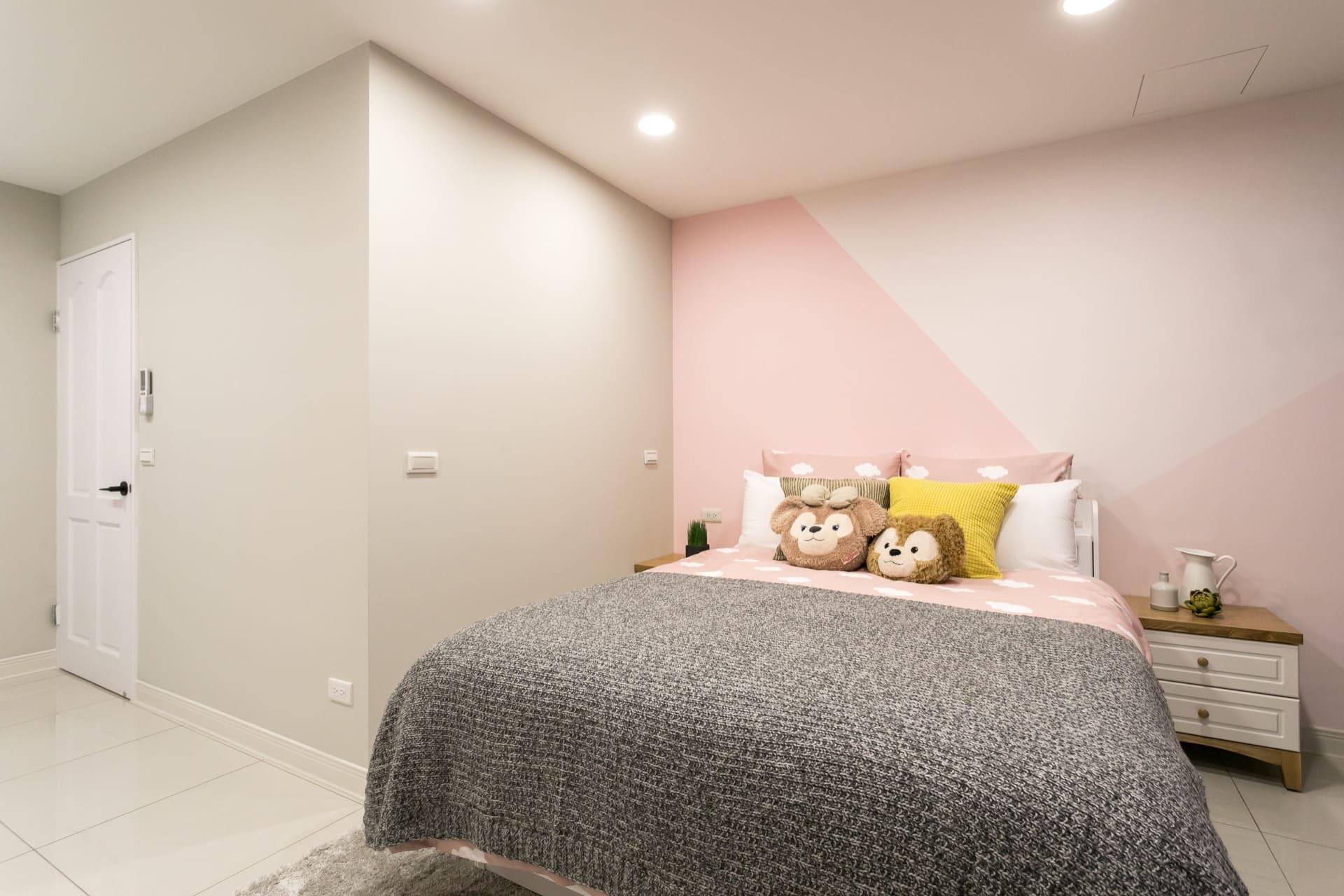 床頭牆面彩色造型。照片左側為外觀經過烤漆處理的白色門片,耐磨耐髒